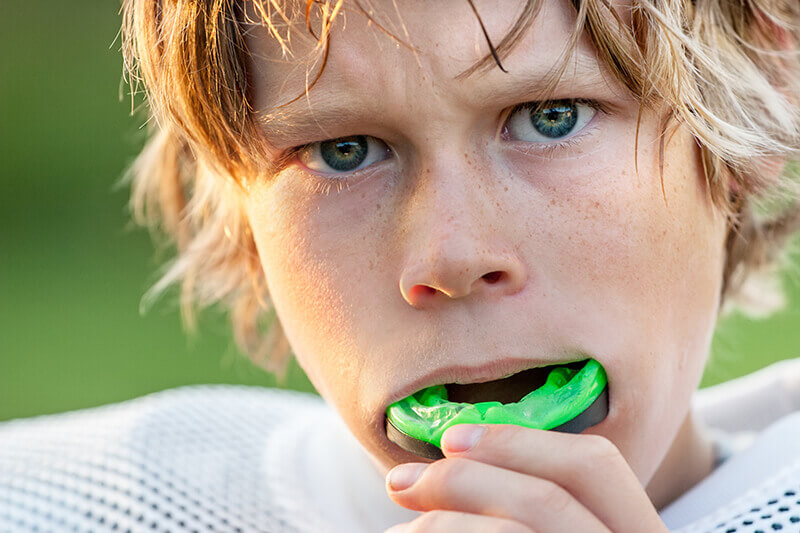 young man with mouth guard benefits from general dentistry