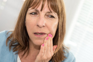 woman touching her jaw has tooth decay problem