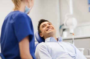 Man in dentist chair smiling because he knows how to prevent tooth decay